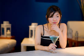 A picture of a pretty young asian woman sitting alone at a table